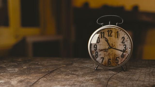 Bild eines alten Weckers auf einem Holztisch als Symbol der Verweildauer